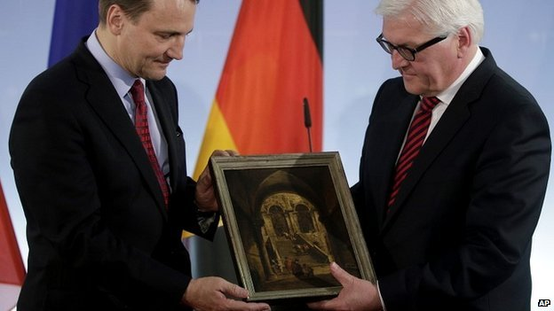 """German Foreign Minister Frank-Walter Steinmeier (R) passes the """"Palace Stairs"""" painting to his Polish counterpart Radoslaw Sikorski"""