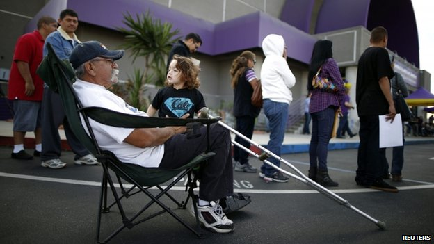 Juan Ortiz, 67, and his 18-month-old grandson wait in line at a health insurance enrolment event in Commerce, California, on 31 March 2014