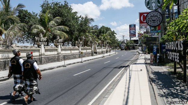 An empty street patrolled by traditional guards on Nyepi in Bali