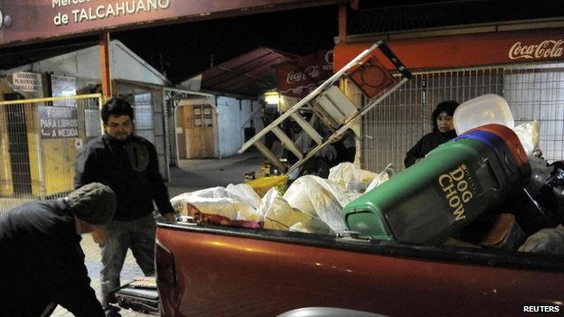 Residents take their belongings to higher ground after a Tsunami alarm at Talcahuano city, south of Santiago