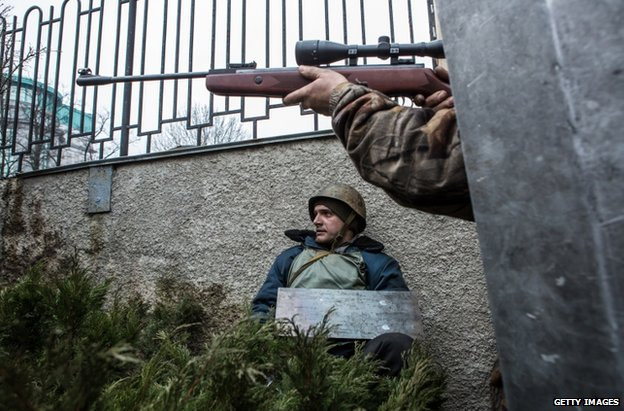 An opposition activist aims a rifle in Kiev, 20 April