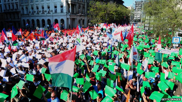 People hold coloured papers to create a giant Hungarian tricolor as sympathisers and party members of the opposition party attend in front of the building of the Hungarian State Opera in Budapest