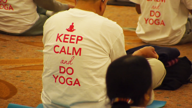 """NRI conference in London, with a t-shirt saying """"keep calm and do yoga""""."""