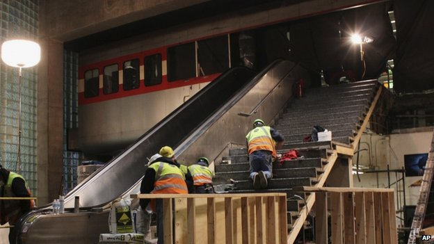 Workers repair the escalator and surrounding areas where a CTA commuter train crashed at O'Hare International Airport (28 March 2014)