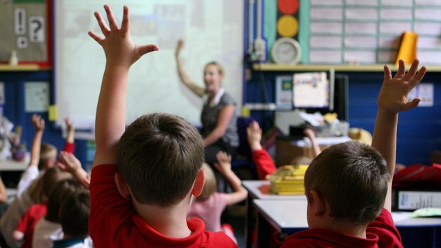 Children raise their hands in class