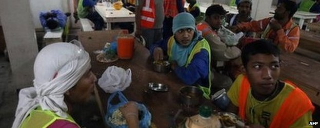 Migrant labourers have a lunch break as they work on a construction site on October 3, 2013 in Doha in Qatar