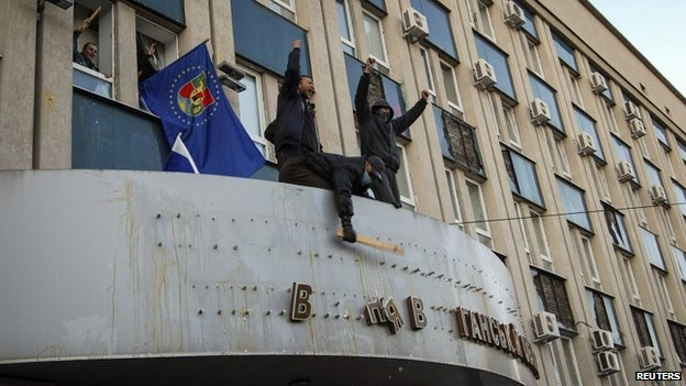 Pro-Russian protesters remove the sign from the state security service building in Luhansk, eastern Ukraine, on 6 April 2014