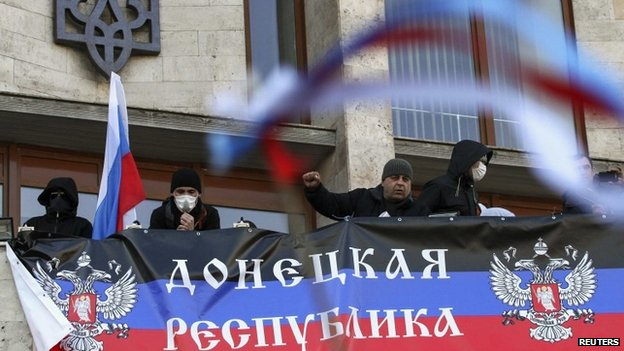 Pro-Russia protesters hang a banner as they storm the regional government building in Donetsk April 6, 2014
