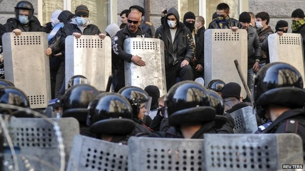 Pro-Russian protesters (top) stand in front of riot police near the regional government building in Donetsk April 6, 2014