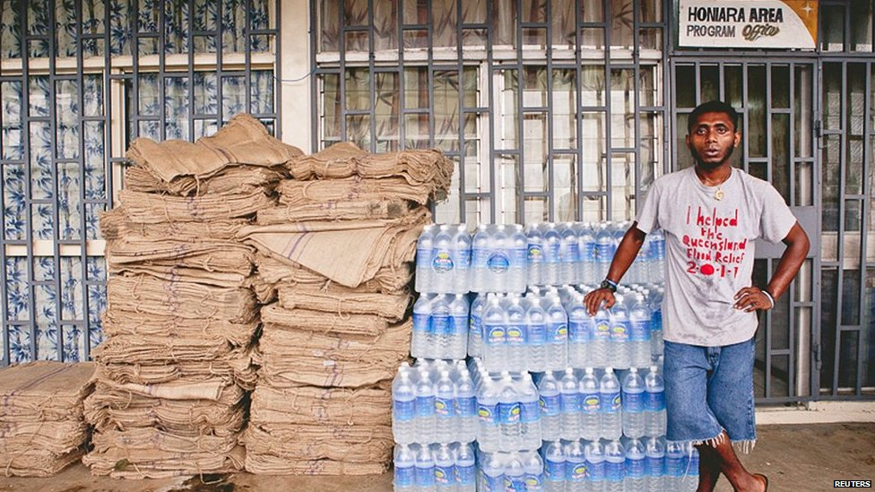 A relief worker stands next to supplies of blankets and water at a distribution centre after severe flooding in the capital Honiara in the Solomon Islands in this picture released by World Vision on 6 April, 2014