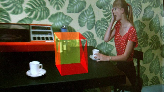 A woman sitting next to a computer generated box on a table