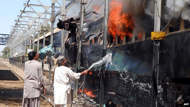 A Pakistani railway official tries to extinguish the fire on the train at Sibi railway station - 8 April 2014