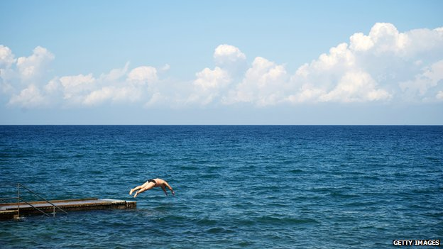 A swimmer jumps into the sea in the Adriatic town of Izola in September 2013.