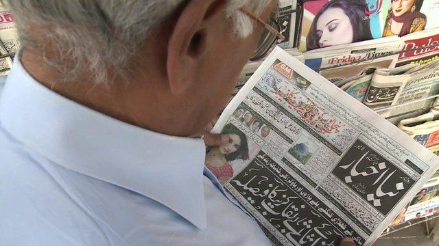 A man reads a newspaper in Pakistan