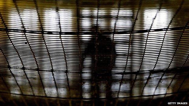 A prisoner at HMP Pentonville walks through an atrium May 19, 2003 in London