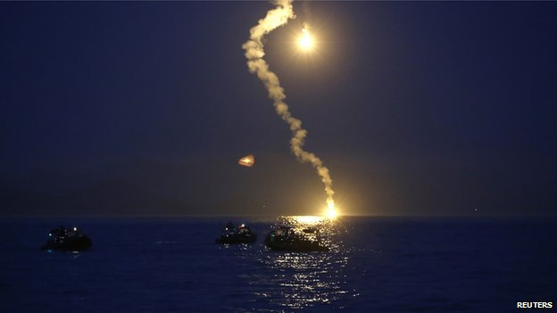 Maritime police search for missing passenger as lighting flares are released for a night search on 16 April 2014.