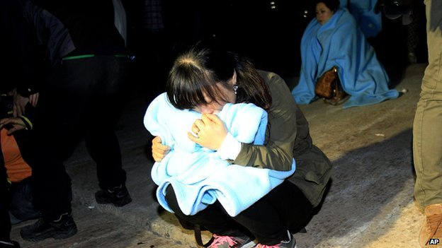 Relative cries as she waits for missing passengers at a port in Jindo, South Korea, on 16 April 2014