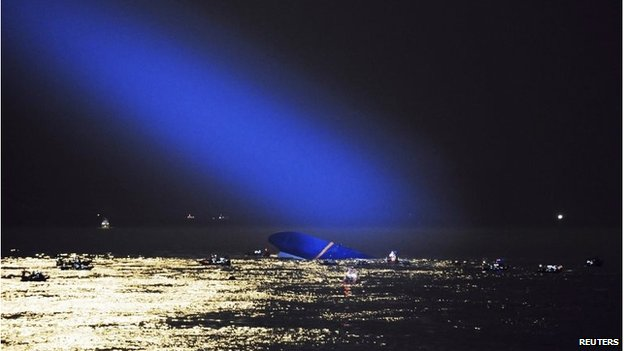 The wreck, lit up by a helicopter's spotlight at night
