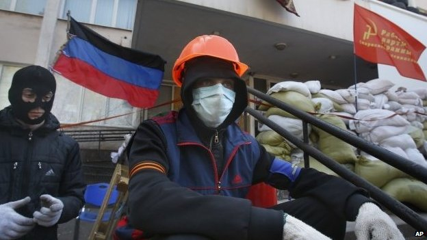 Masked pro-Russian protesters guard a barricade in front of the city hall in Mariupol, eastern Ukraine, Thursday, April 17, 2014