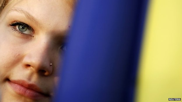 Pro-Kiev protester looks on behind a Ukrainian flag during a rally in Donetsk, in eastern Ukraine April 17, 2014