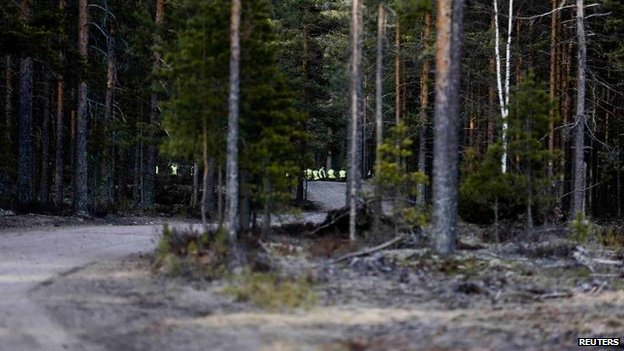 Rescuers are seen through the trees at the Jamijarvi airport site, 20 April