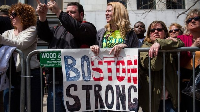 """Fans with a """"Boston Strong"""" poster cheer on runners as they finish the Boston Marathon on April 21, 2014 in Boston, Massachusetts"""