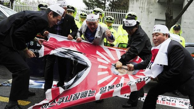 """South Korean protesters tear a Japanese wartime flag during a rally to protest against Japanese lawmakers"""" visit to Yasukuni Shrine"""