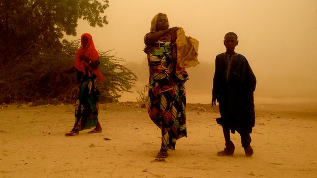Women and child from the Nigerian village of Gashagar wade through sandstorm on Niger side of the border, where they sought refuge