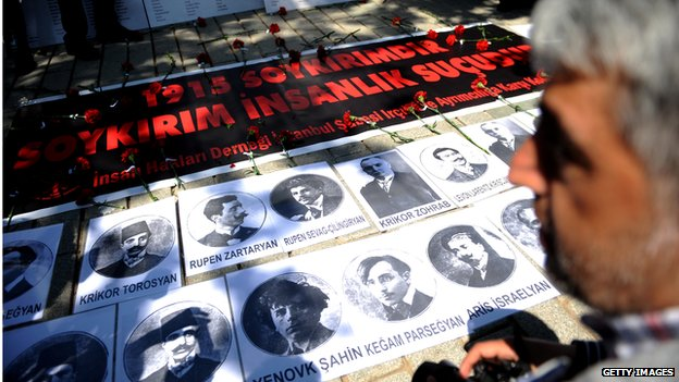 "A person looks at portraits and a sign reading ""1915 is a Genocide. Genocide is a crimes against humanity"" during a demonstration on 24 April 2013 in Istanbul"