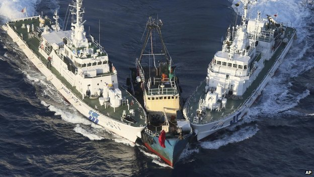 The Boa Diao boat (C) is surrounded by Japan Coast Guard patrol boats after Hong Kong activists descended from the boat onto Uotsuri Island, one of the East China Sea islands, on 15 August 2012