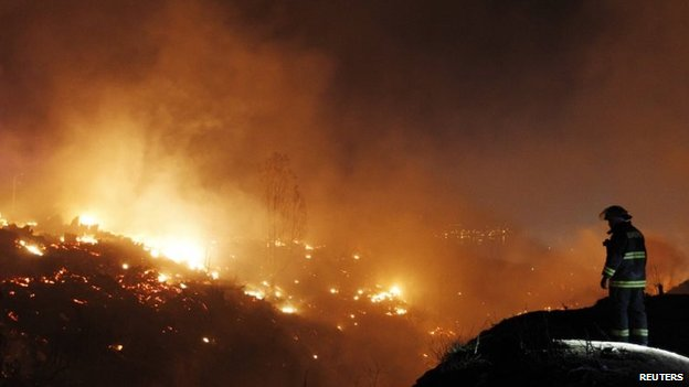 Firefighter work to put out a fire in Valparaiso city, northwest of Santiago on 13 April, 2014