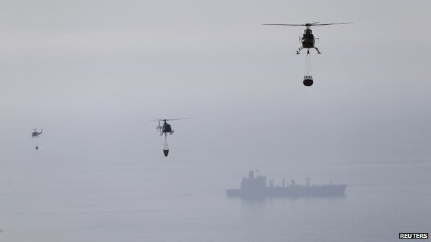Helicopters pick up water from the Pacific Ocean to dump on the smouldering remains of houses after a fire burned several neighbourhoods in the hills in Valparaiso city on 14 April, 2014.