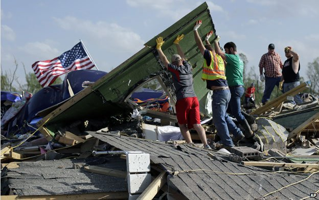 Friends and family sift through debris at a collapsed home in Vilonia, Arkansas