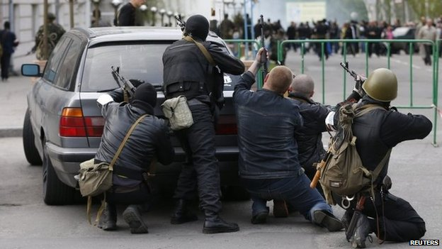 Pro-Russia armed men take cover behind a car near the headquarters of the local police in Luhansk (29 April 2014)