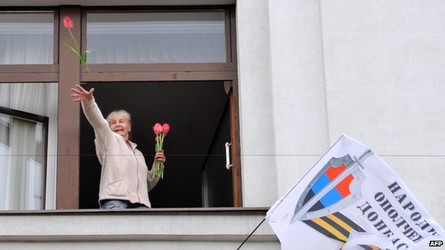 A pro-Russia activist throws flowers from a the regional administration's headquarters in Luhansk (29 April 2014)