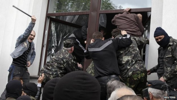 Pro-Russian activists climb into the regional government's headquarters in Luhansk (29 April 2014)