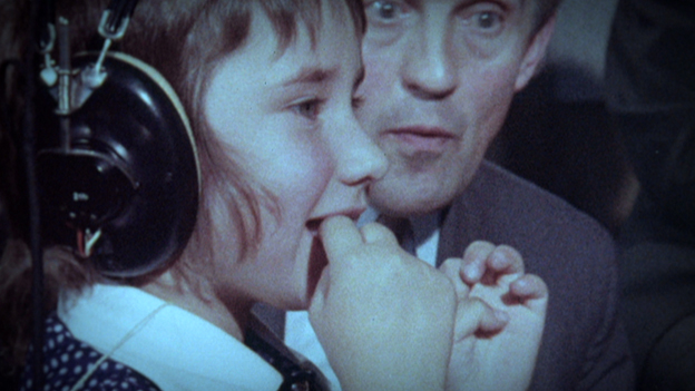 A young girl has headphones on and is watching something out of shot