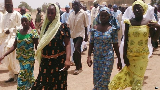 Four female students of the government secondary school Chibok, who were abducted by gunmen and reunited with their families, walk in Chibok, Nigeria (21 April 2014)