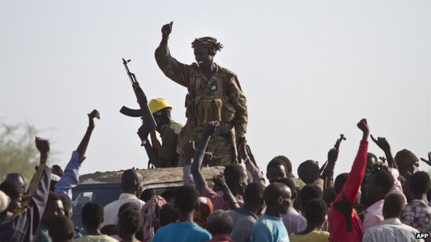 A government soldier waves his AK-47 in celebration outside the UN base in Malakal after the army said it had recaptured the town from rebels on 19 March 2014