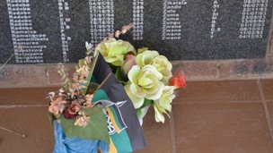 Flowers on the foot of the memorial with an ANC flag