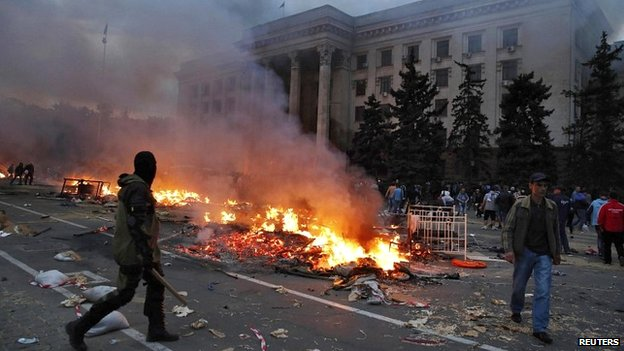 A protester walks past a burning pro-Russian tent camp near the trade union building in Odessa - 2 May 2014