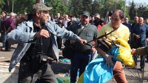 Pro-Russian activist and a pro-Ukraine supporter scuffle for a Ukrainian flag in Odessa
