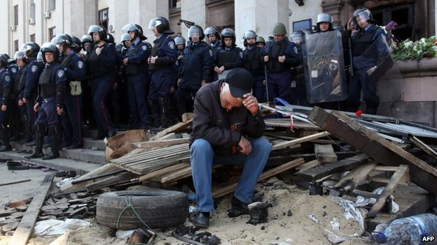 Pro-Russian activist sits in front of the burned out trade union building in Odessa, 3 May 2014