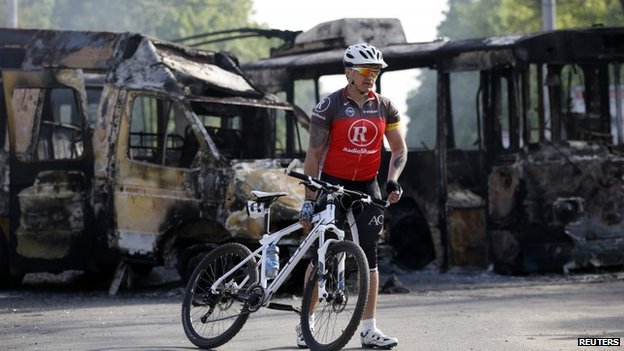 Cyclist with burned out vehicles in Kramatorsk, 3 May 2014