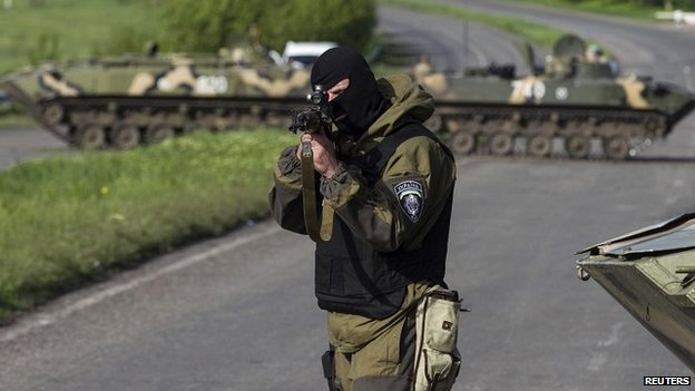 A Ukrainian soldier points his weapon at an approaching car at a checkpoint near Sloviansk - 3 May 2014