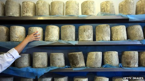 A cheesemaker checks on their produce