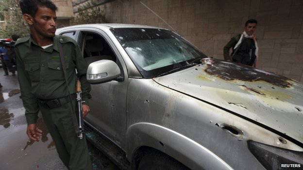Policemen stand by a damaged car where a French man was assassinated, in Sanaa May 5