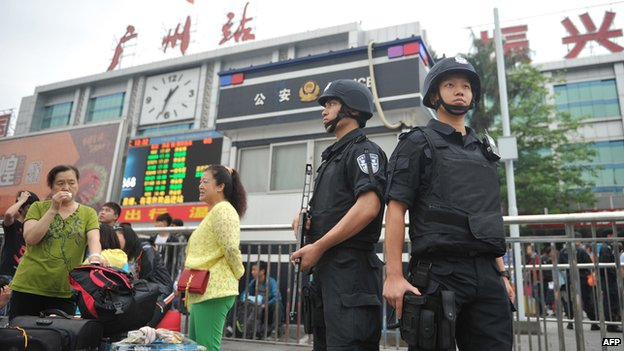 Members of a Chinese SWAT team stand guard on the square of Guangzhou railway station after a knife attack outside the station in Guangzhou, in southern China's Guangdong province on 6 May 2014