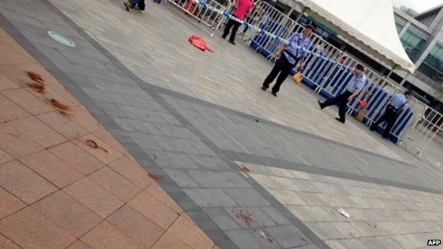 Security personnel tape off the scene of a knife attack on the square of Guangzhou railway station after a knife attack in Guangzhou, in southern China's Guangdong province on 6 May 2014