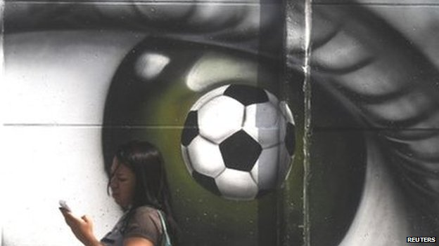 A woman walks past a graffiti of an eye and a soccer ball in Sao Paulo